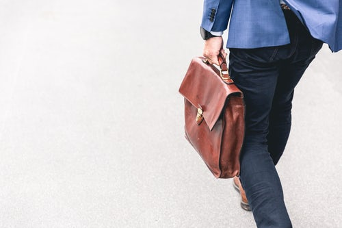 man carrying brown bag to a conference