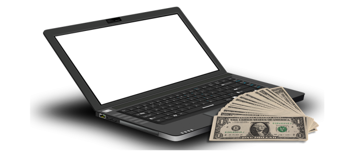 laptop and some dollars on the table