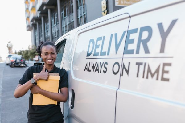 lady stands beside delivery van in Nigeria
