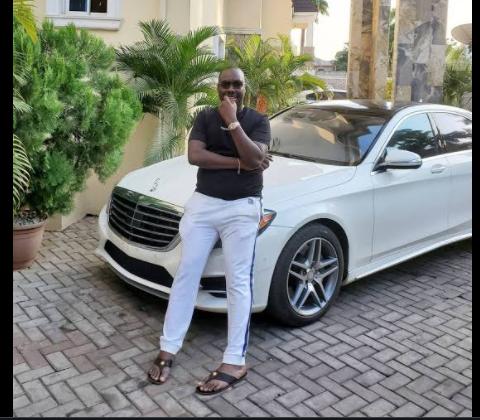 Obi Cubana poses with white Mercedes Benz